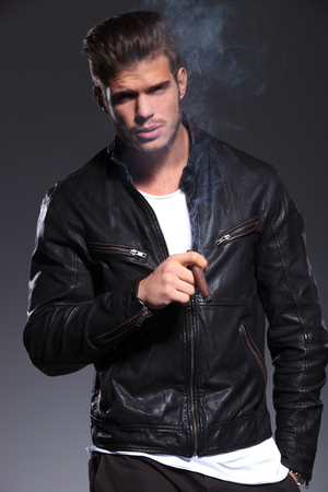 young man in leather jacket is blowing the smoke and looks at the camera