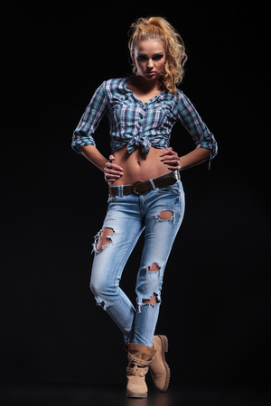 full body picture of a young fashion blonde woman with hands on hips photo