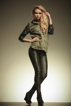 young fashion blonde woman in leather pants posing and looking away from the camera photo