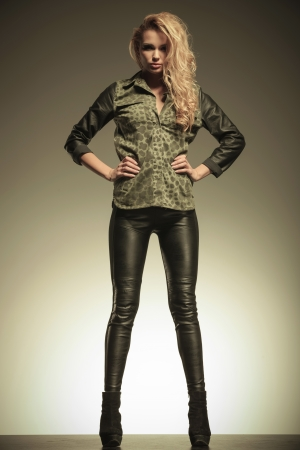 hot pants: beautiful young blonde woman in leather pants posing with hands on hips