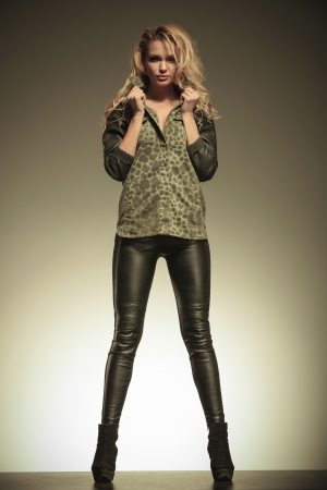fashion blonde woman in leather pants posing by holding her collar  photo