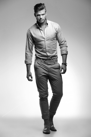 toward: black and white full length picture of a young casual man walking toward the camera Stock Photo