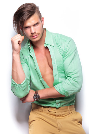 closeup portrait of a young casual man wearing an unbuttoned shirt, revealing his nice muscles, while looking into the camera. on white background photo