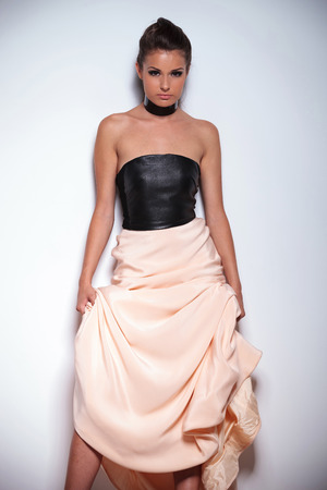 sexy party girl: young attractive woman leaning against a wall and holding up her beautiful gown