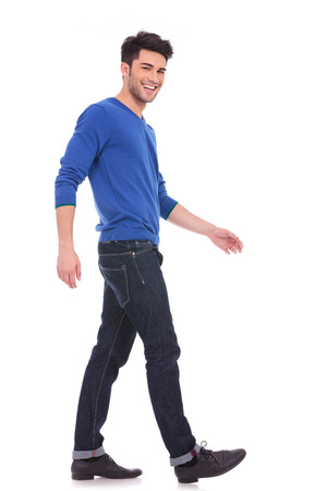 side view of a young man laughing and walking while looking at the camera, full body picture photo
