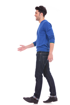 see side: side view of a casual man in blue jeans and shirt walking on white background