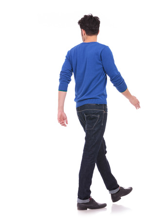 see side: back view of a walking casual man looking to a side on white background