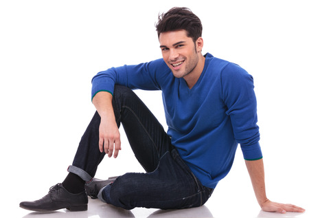 relaxed casual man sitting on white background and looking at the camera Stock Photo - 23422851