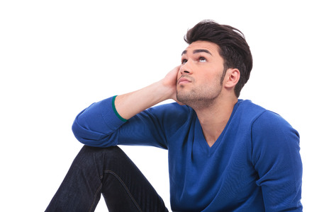 thoughtful young casual man sitting and looking up at something on white background photo