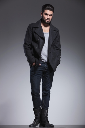 greatcoat: full body picture of a fashion man with beard standing with hands in pockets and looking away from the camera Stock Photo
