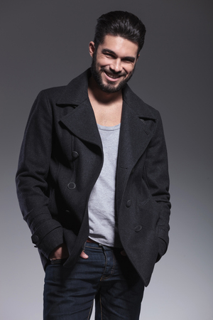 greatcoat: young man with long beard in an overcoat smiling to the camera and standing with hands in pokets
