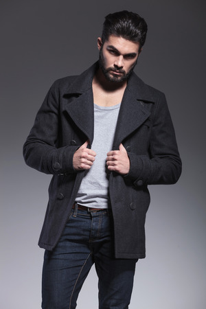 greatcoat: young fashion bearded man holding his long coat and posing for the camera Stock Photo