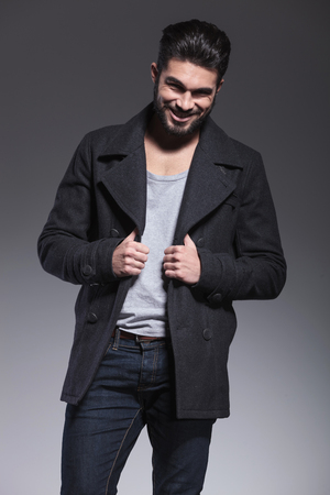 greatcoat: happy young bearded fashion man is smiling at the camera on gray background