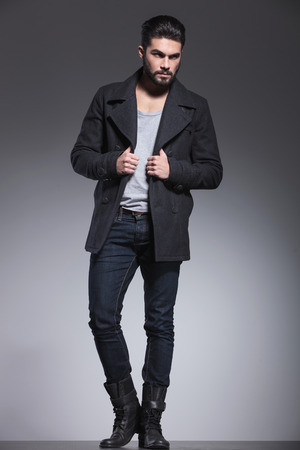 greatcoat: young man with long beard is holding his coats collar and looks away