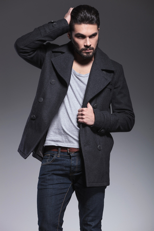 greatcoat: young bearded man passing his hand through his hair and looks away from the camera