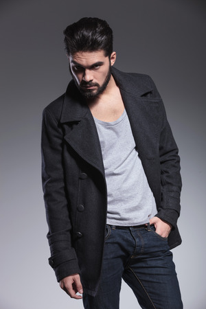 young bearded man in long coat is posing with one hand in his pocket Stock Photo