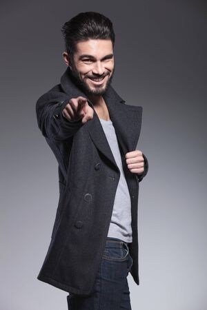 greatcoat: young bearded man is smiling and pointing his finger to the camera