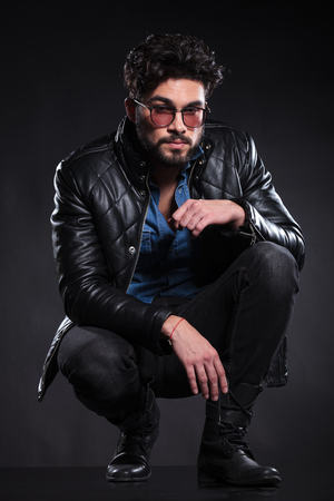 crouched: young fashion man with glasses in a leather jacket standing crouched on dark background