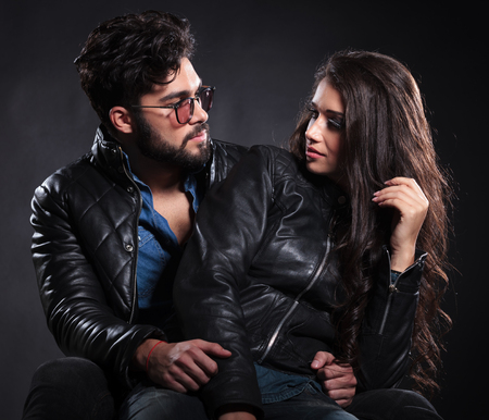 fashion man and woman looking at each other with love on dark background photo