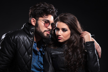 pensive man with glasses and long beard embracing his girlfriend and looks away from the camera photo