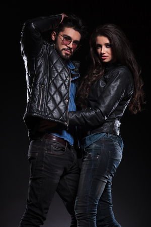 young couple in leather jackets in a fashion pose on dark background, man passing his hand through his hair photo