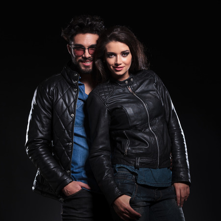 fashion woman in leather jacket standing against her boyfriend, both looking at the camera an smile
