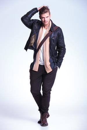 젊은 패션 모델이 카메라에 자신의 머리를 그의 손을 전달하고 미소의 전신 사진