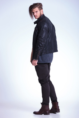 full: Vista posterior de un hombre de moda joven con una chaqueta de cuero que mira a la c�mara