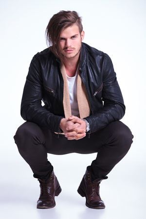 crouched: smiling young man in leather jacket standing crouched on light gray studio backgroun