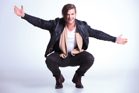 crouched: happy young man in leather jacket jumps welcomes you, on a light gray background