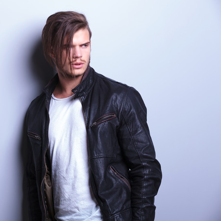 fashion man in leather jacket looks away from the camera while standing against a gray wall photo