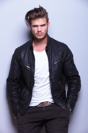 serious young man in leather jacket standing against gray wall looks at the camera photo