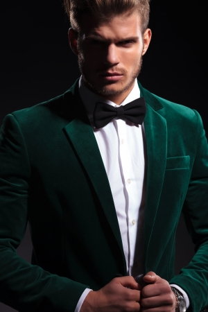 hair bow: elegant fashion man in velvet suit and neck bow looking at the camera while posing on black background Stock Photo