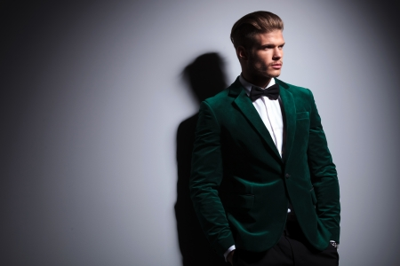 elegant business man: relaxed young fashion model in green velvet elegant suit with neck bow tie looking away from the camera white standing with his hands in pockets Stock Photo