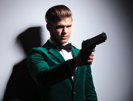 James Bond wannabe young assasin pointing his big pistol to something on gray background