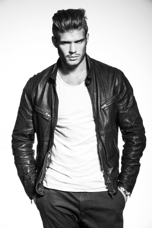 male fashion: black and white picture of a young fashion model in leather jacket standing with his hands in his pockets