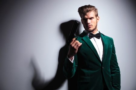 james bond: young man in elegant green velvet suit holding a big gun and looks away from the camera Stock Photo