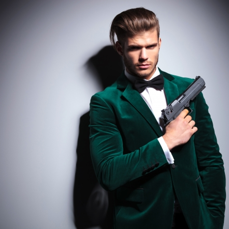 assasin: James Bond wannabe young assasin with a big pistol in his hand Stock Photo