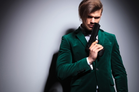 hitman: young elegant hitman  waiting in green velvet suit with neck bow Stock Photo