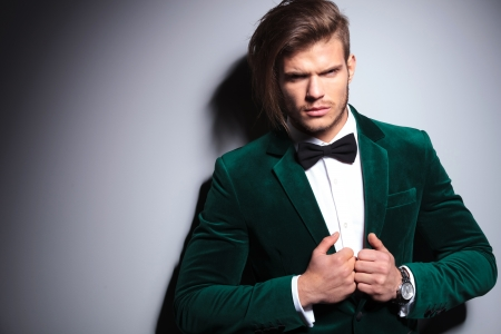 neck tie: angry young man in green velvet suit looks at the camera on gray background