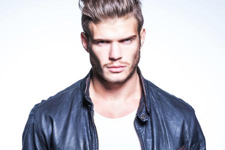poses de modelos: foto de primer plano de un modelo de moda joven en la chaqueta de cuero que mira a la c�mara