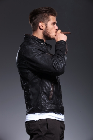 hombre fumando puro: vista lateral de un hombre de moda en la chaqueta de cuero con el cigarro en la boca, listo para fumarlo