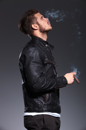 side view of a young man in leather jacket smoking and blowing the smoke photo