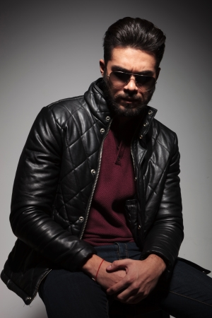 unshaved: dramatic shot of a young man with beard in leather jacket and sunglasses