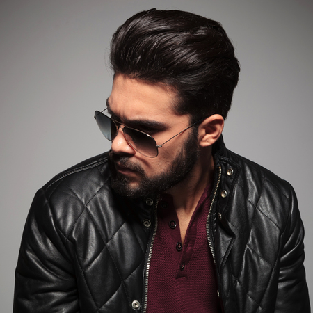 unshaved: profile of a young man in sunglasses and leather jacket looking away from the camera