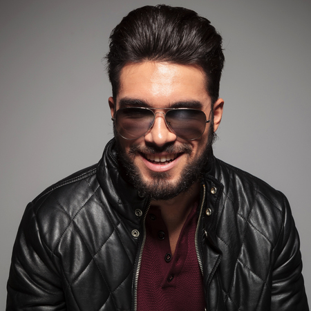 man with long beard smiling to the camera while wearing sunglasses and leather jacket photo