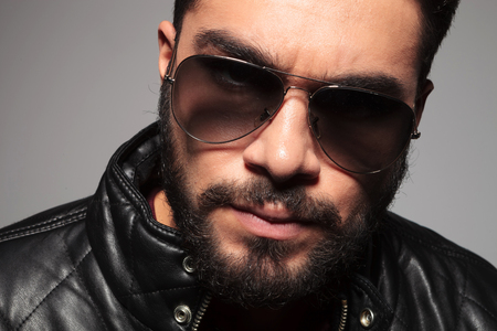 closeup picture of a young man with long beard wearing sunglasses and leather jacket looking at the camera photo