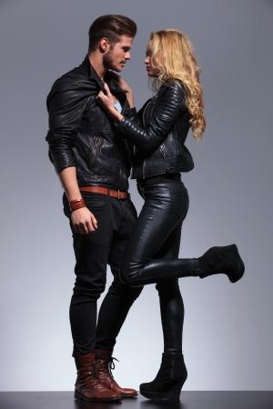 회색 배경에 서로를 찾고 젊은 패션 커플의 측면보기