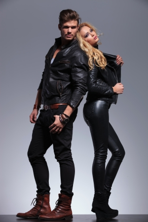 young fashion couple in leather clothes standing back to back  photo