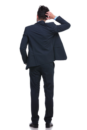 back of a young business man scratching his head trying to resolve a problem Stock Photo